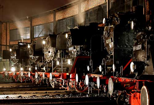 Dampflok-Giganten vor dem beleuchteten Rundlokschuppen