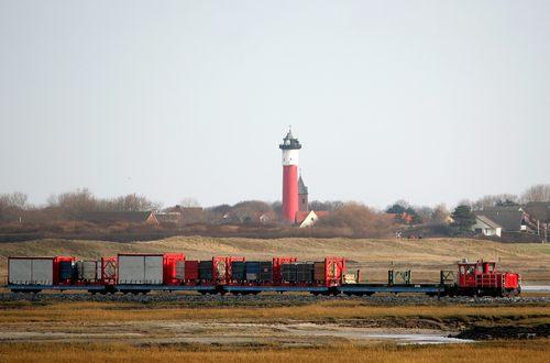 Inselbahn-Güterzug vor altem Leuchtturm